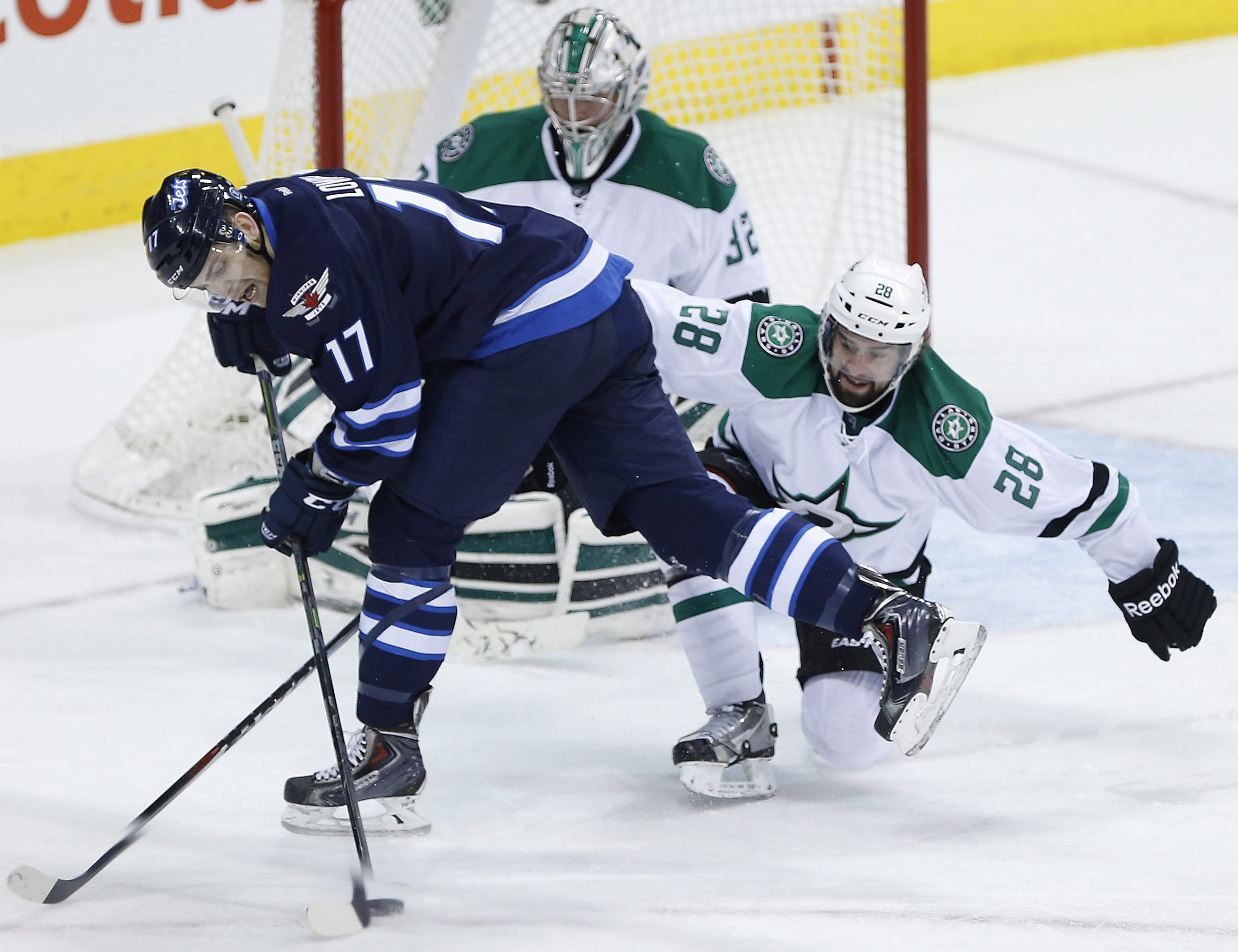 Winnipeg Jets' Adam Lowry (17) can't get the shot away on Dallas Stars goaltender Kari Lehtonen (32) as David Schlemko (28) defends during the third period of an NHL hockey game in Winnipeg, Manitoba, on Saturday, Jan. 31, 2015. (AP Photo/The Canadian Press, John Woods)